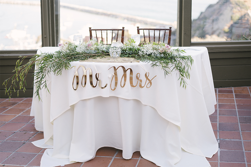 Dana point outdoor beach wedding at cannons seafood grill reception table set up white table linen with greenery garland decor in the center with white babys breath centerpiece decor in clear vase with white place settings and glassware wit h brown chiavari chairs and gold decor