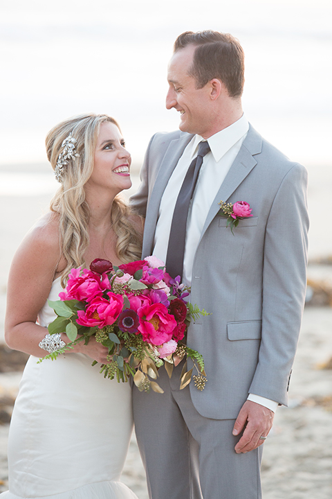 Orange county beach wedding shoot at pasea hotel bride form fitting mermaid style strapless gown with a straight neckline and silk detail with groom grey notch lapel suit with white dress shirt and long black skinny tie with bright pink floral boutonniere standing and hugging bride holding bright pink floral bridal bouquet