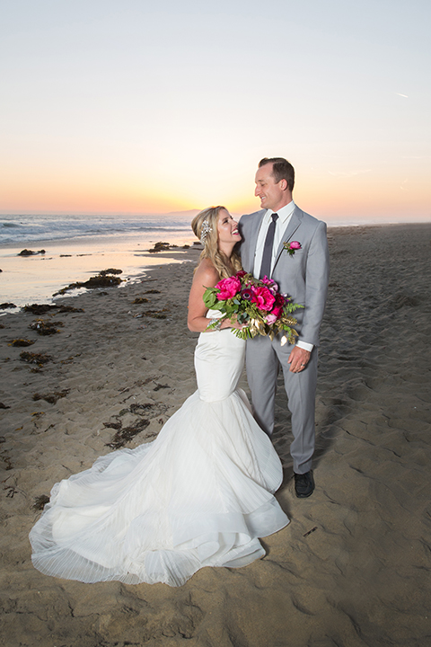 Orange county beach wedding shoot at pasea hotel bride form fitting mermaid style strapless gown with a straight neckline and silk detail with groom grey notch lapel suit with white dress shirt and long black skinny tie with bright pink floral boutonniere standing on the beach and hugging bride holding bright pink floral bridal bouquet