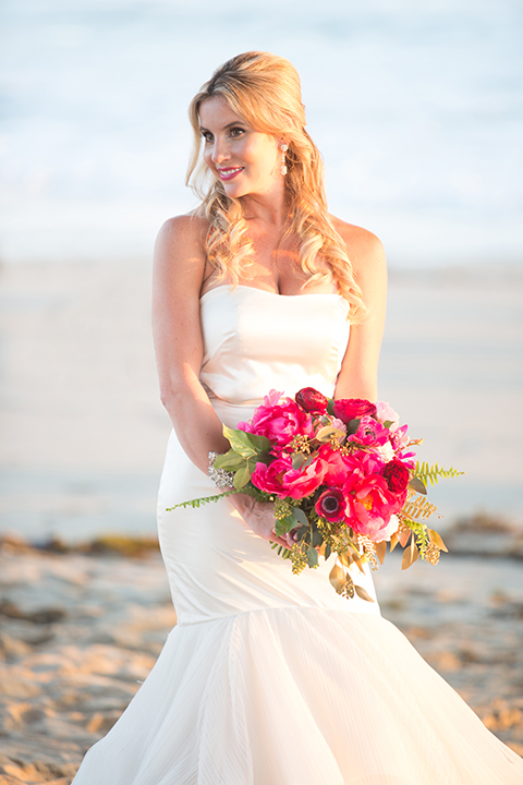 Orange county beach wedding shoot at pasea hotel bride form fitting mermaid style strapless gown with a straight neckline and silk detail holding bright pink floral bridal bouquet