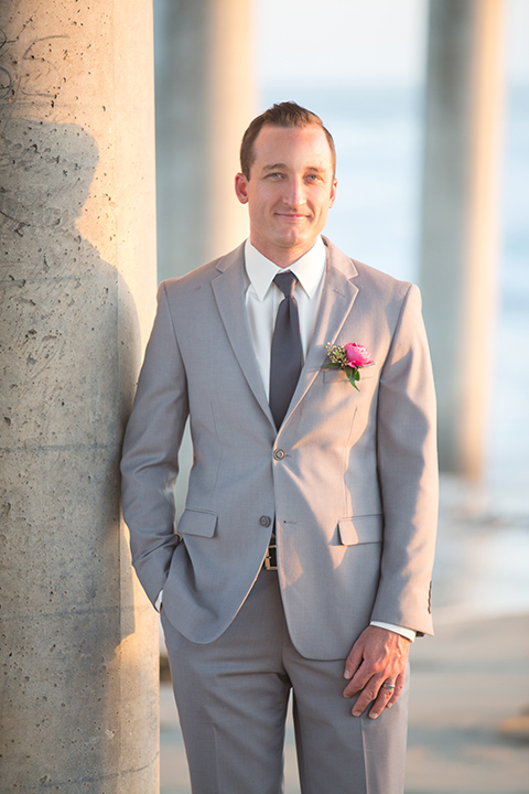 Orange county outdoor beach wedding shoot at the pasea hotel groom grey notch lapel suit with white dress shirt and long black tie with bright pink floral boutonniere standing with hands in pockets on the beach