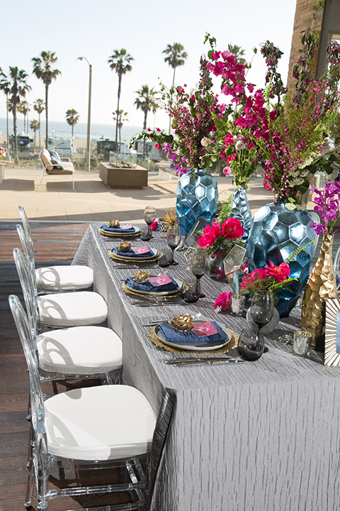 Orange county outdoor beach wedding at the pasea hotel table set up with light grey table linen and gold place settings with navy napkins and bright pink menus with gold flower decor on top and black wine glasses with blue and gold centerpiece decor and bright pink flowers with clear ghost chairs