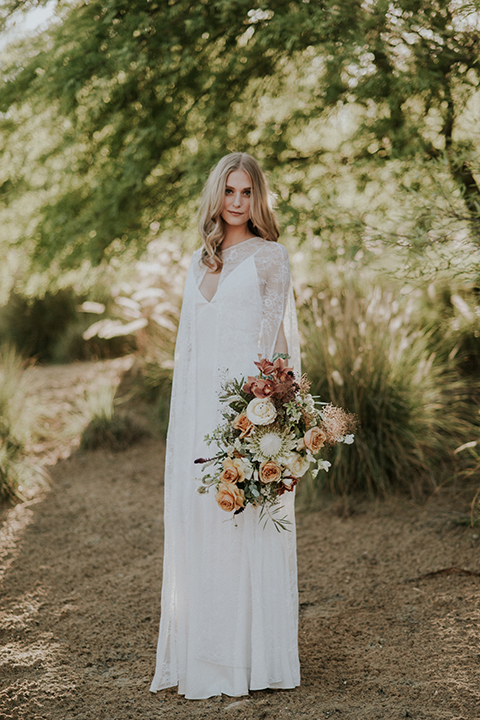 San diego outdoor wedding shoot at the san diego zoo and safari park bride white chiffon gown with lace sleeves and thin straps with plunging neckline holding white and orange floral bridal bouquet