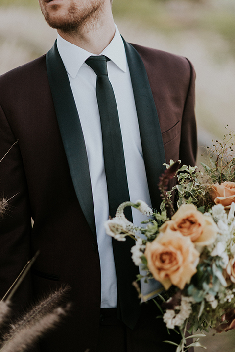San diego outdoor wedding shoot at the san diego zoo and safari park groom burgundy tuxedo with black shawl lapel and white dress shirt with long black skinny tie and black shoes holding white and orange floral bridal bouquet close up