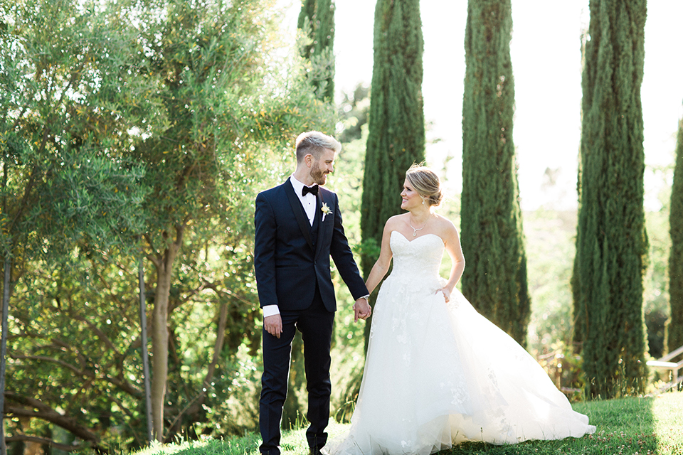 Temecula outdoor wedding at mount palomar bride strapless ball gown with tulle skirt and sweetheart neckline with lace and beading detail with groom navy blue shawl lapel tuxedo with matching vest and white dress shirt with black bow tie and white floral boutonniere holding hands