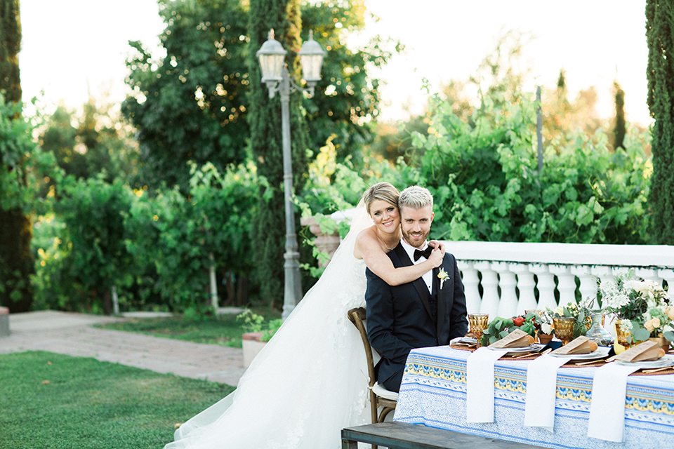 Temecula outdoor wedding at mount palomar bride strapless ball gown with tulle skirt and sweetheart neckline with lace and beading detail with groom navy blue shawl lapel tuxedo with matching vest and white dress shirt with black bow tie and white floral boutonniere sitting at table