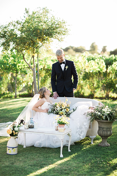 Temecula outdoor wedding at mount palomar bride strapless ball gown with tulle skirt and sweetheart neckline with lace and beading detail with groom navy blue shawl lapel tuxedo with matching vest and white dress shirt with black bow tie and white floral boutonniere bride sitting and holding white and green floral bridal bouquet