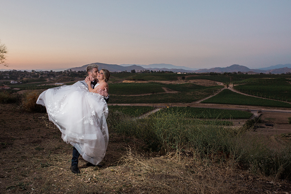 Temecula outdoor wedding at mount palomar bride strapless ball gown with tulle skirt and sweetheart neckline with lace and beading detail with groom navy blue shawl lapel tuxedo with matching vest and white dress shirt with black bow tie and white floral boutonniere groom carrying bride