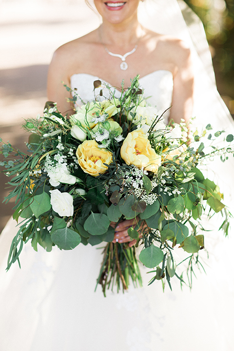 Temecula outdoor wedding at mount palomar bride strapless ball gown with tulle skirt and sweetheart neckline with lace and beading detail holding white and green floral bridal bouquet close up