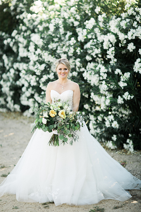 Temecula outdoor wedding at mount palomar bride strapless ball gown with tulle skirt and sweetheart neckline with lace and beading detail holding white and green floral bridal bouquet