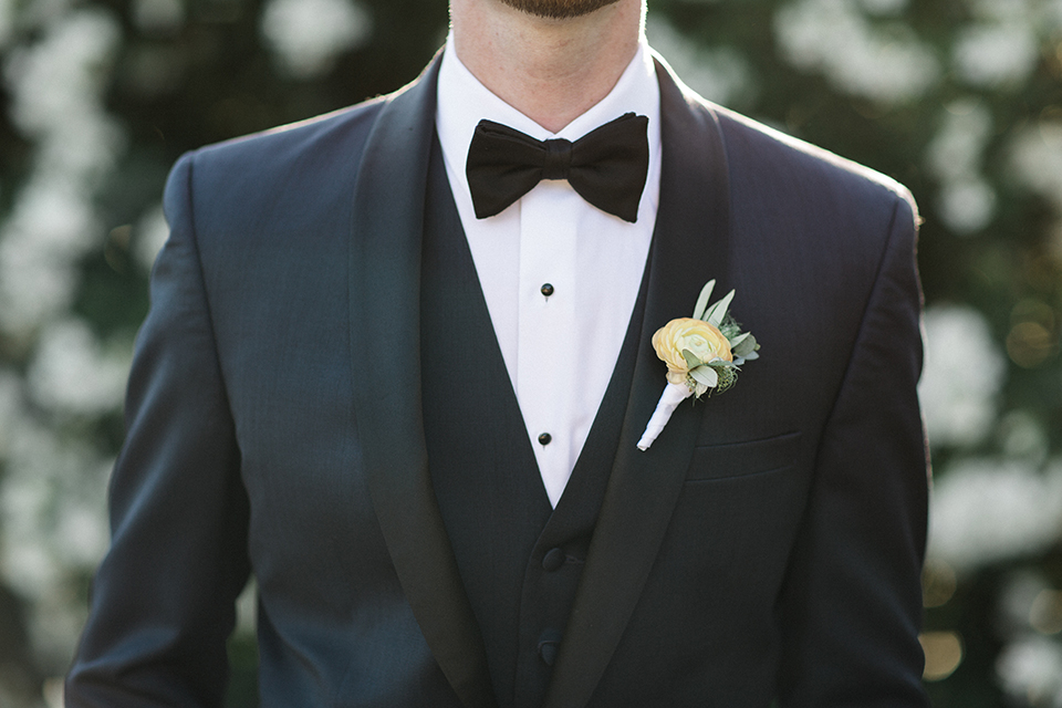 Temecula outdoor wedding at mount palomar winery groom navy blue shawl lapel tuxedo with matching vest and white dress shirt with black bow tie and white floral boutonniere close up