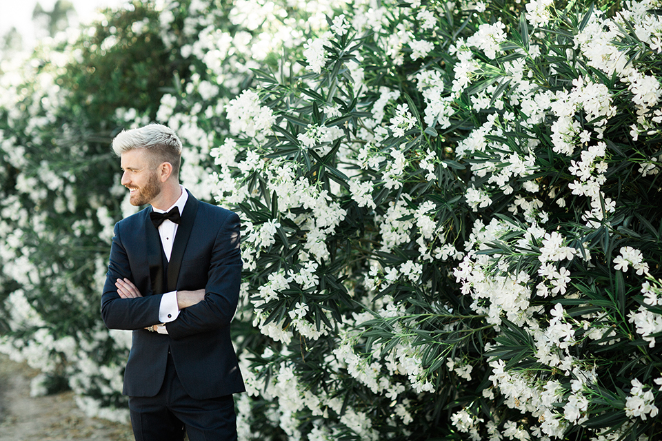 Temecula outdoor wedding at mount palomar winery groom navy blue shawl lapel tuxedo with matching vest and white dress shirt with black bow tie and white floral boutonniere