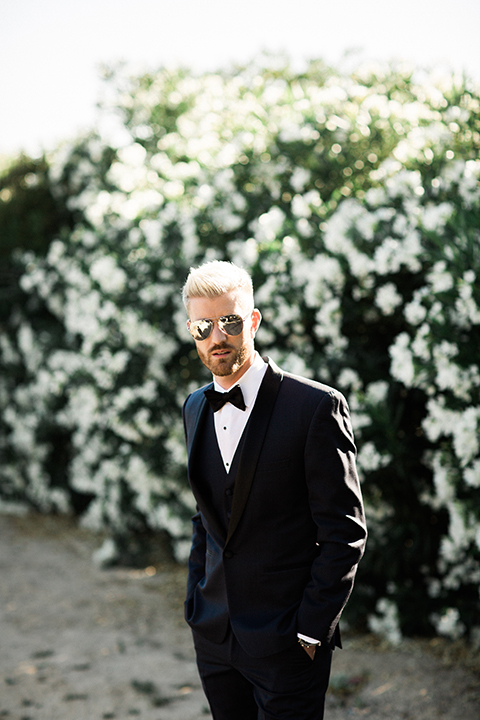 Temecula outdoor wedding at mount palomar winery groom navy blue shawl lapel tuxedo with matching vest and white dress shirt with black bow tie and white floral boutonniere wearing sunglasses