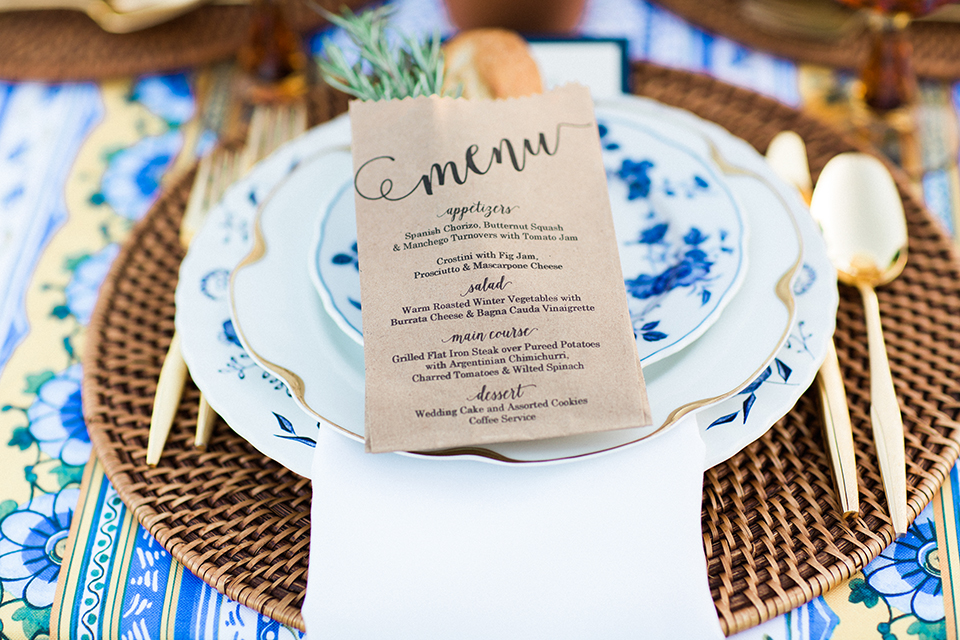 Temecula outdoor wedding at mount palomar winery table set up light brown wood table with white and blue patterned table linen and white place settings on top of wicker place mates with white and green flower centerpiece decor with white chairs and gold wine glasses