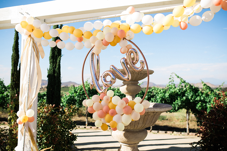 Temecula outdoor wedding at mount palomar winery table set up light brown wood table with white and blue patterned table linen and white place settings on top of wicker place mates with white and green flower centerpiece decor with white chairs and gold wine glasses with yellow and white balloons and love sign