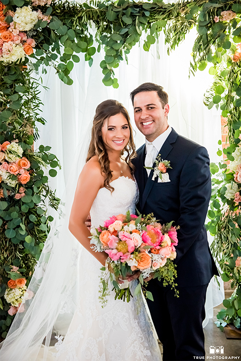 San diego outdoor wedding at the brick bride strapless form fitting gown with a sweetheart neckline and long lace veil with groom cobalt blue notch lapel suit with matching vest and white dress shirt with long white tie and matching pocket square with light pink floral boutonniere hugging and holding pink and orange floral bridal bouquet