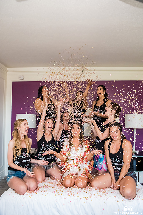 San diego outdoor wedding at the brick bride getting ready with bridesmaids white floral silk robe with bridesmaids black tank tops with gold writing throwing confetti on the bed wedding photo idea for bride and bridesmaids getting ready