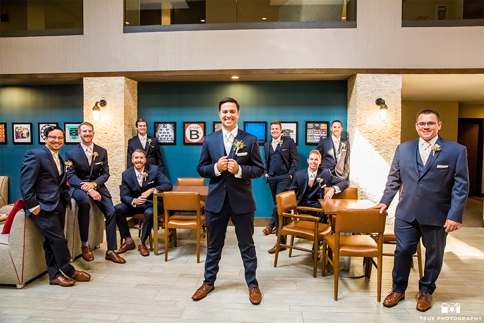 San diego outdoor wedding at the brick groom cobalt blue notch lapel suit with matching vest and white dress shirt with long white tie and light orange floral boutonniere with white pocket square with groomsmen cobalt suits with long ties sitting around groom