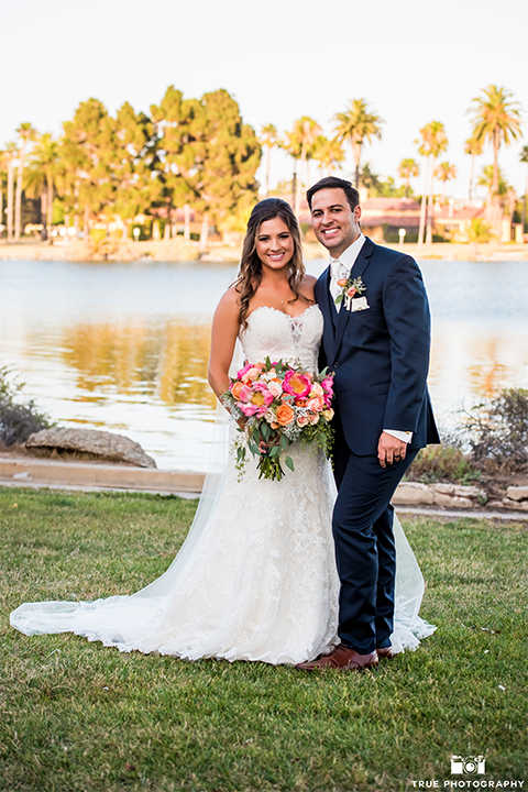 San diego outdoor wedding at the brick bride strapless form fitting gown with a sweetheart neckline and long lace veil with groom cobalt blue notch lapel suit with matching vest and white dress shirt with long white tie and matching pocket square with light pink floral boutonniere hugging and bride holding pink and orange floral bridal bouquet