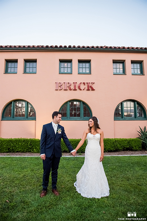 San diego outdoor wedding at the brick bride strapless form fitting gown with a sweetheart neckline and long lace veil with groom cobalt blue notch lapel suit with matching vest and white dress shirt with long white tie and matching pocket square with light pink floral boutonniere holding hands outside venue