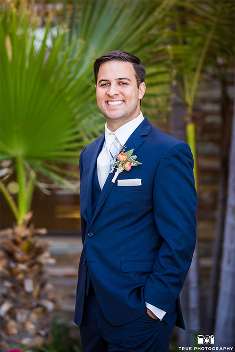 San diego outdoor wedding at the brick groom cobalt blue notch lapel suit with matching vest and white dress shirt with long white tie and light orange floral boutonniere with white pocket square standing with hands in pockets smiling