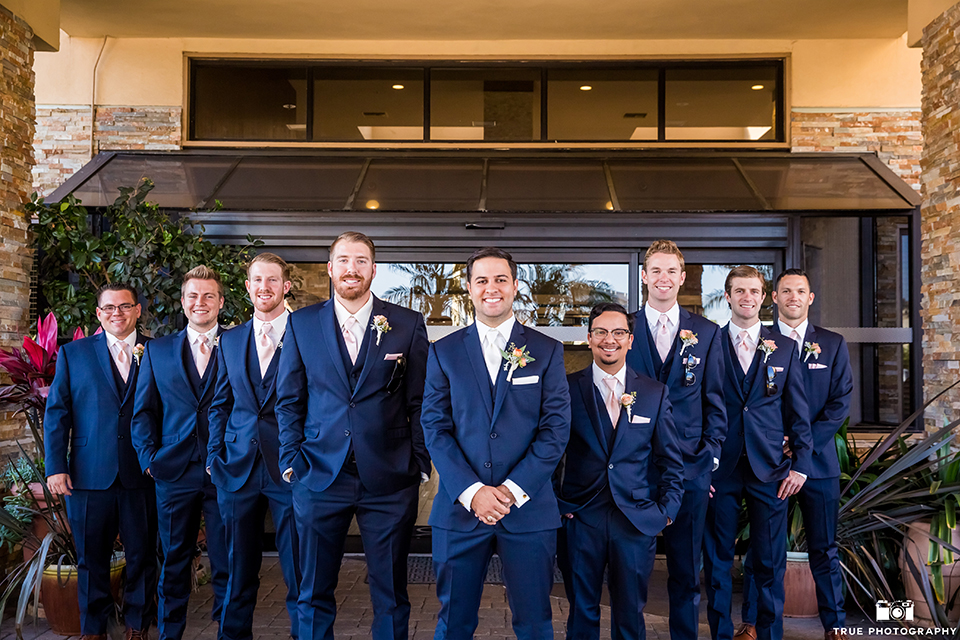 San diego outdoor wedding at the brick groom cobalt blue notch lapel suit with matching vest and white dress shirt with long white tie and light orange floral boutonniere with white pocket square with groomsmen cobalt blue suits with long ties standing with hands crossed