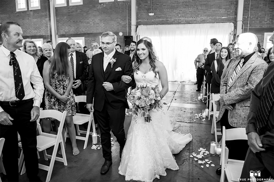 San diego outdoor wedding at the brick bride strapless form fitting gown with a sweetheart neckline and long lace veil holding pink and orange floral bridal bouquet walking down the aisle with dad black and white photo