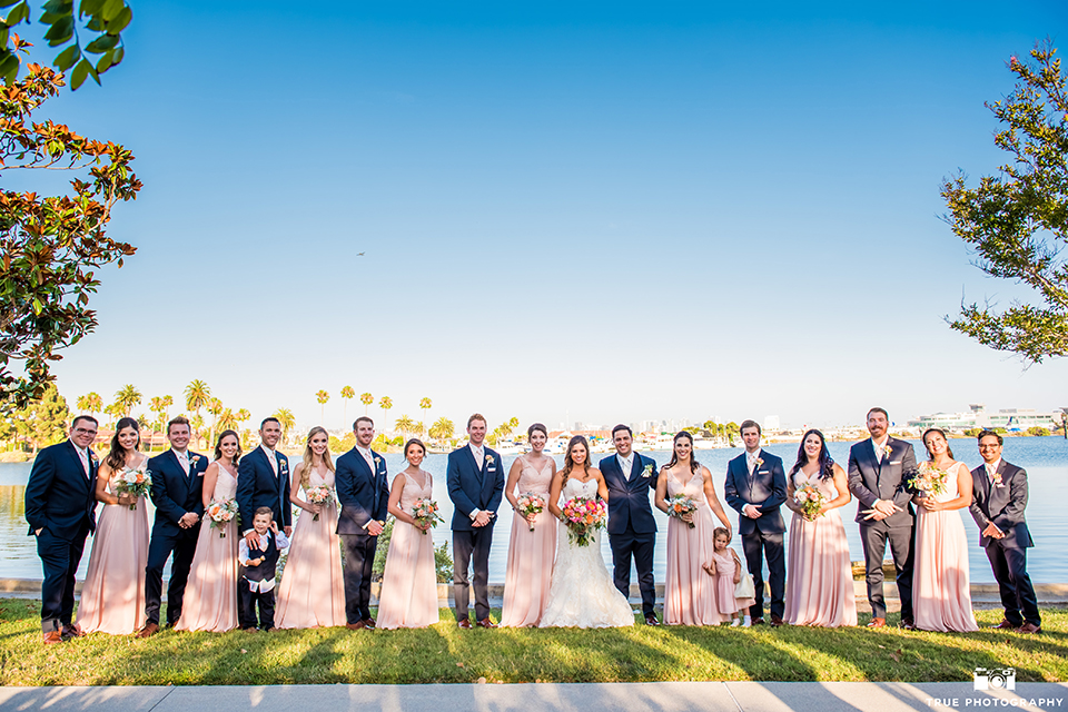 San diego outdoor wedding at the brick bride strapless form fitting gown with a sweetheart neckline and long lace veil with groom cobalt blue notch lapel suit with matching vest and white dress shirt with long white tie and matching pocket square with light pink floral boutonniere with wedding party bridesmaids long pink dresses and groomsmen cobalt blue suits