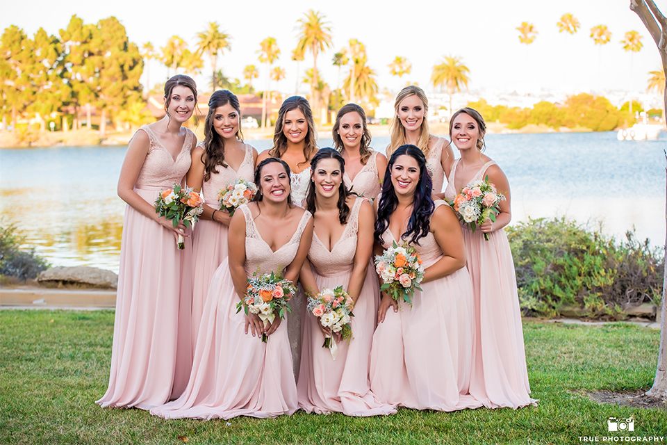 San diego outdoor wedding at the brick bride strapless form fitting gown with a sweetheart neckline and long lace veil holding pink and orange floral bridal bouquet with bridesmaids long pink dresses holding white and green floral bridal bouquets
