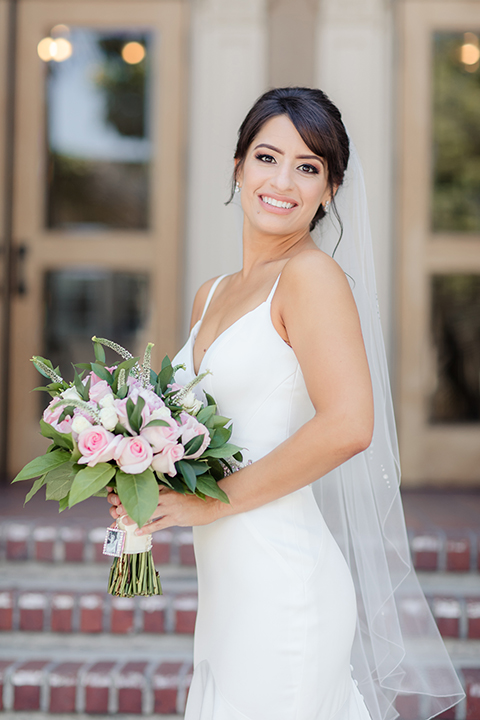 Ebell of long beach outdoor wedding bride form fitting silk gown with a crystal belt and thin spaghetti straps with a sweetheart neckline and crystal belt with a long veil holding white and pink floral bridal bouquet