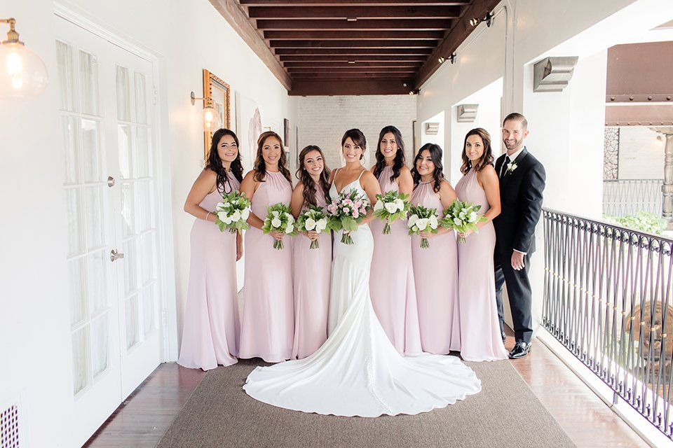 Ebell of long beach outdoor wedding bride form fitting silk gown with a crystal belt and thin spaghetti straps with a sweetheart neckline and crystal belt with a long veil holding white and pink floral bridal bouquet with bridesmaids long blush pink dresses and grooms girl black tuxedo