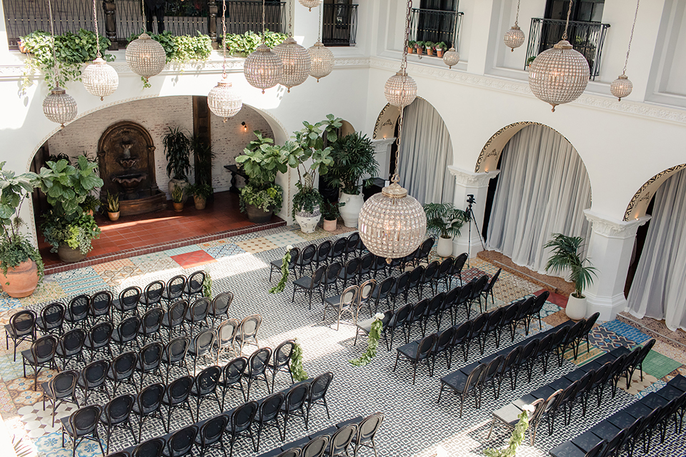 Ebell of long beach outdoor wedding ceremony set up with black chairs and black and white tile ground with white and green floral altar and hanging chandeliers wedding photo idea for ceremony