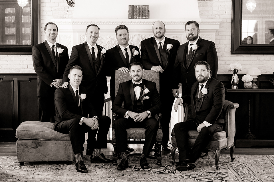 Ebell of long beach outdoor wedding groom black notch lapel tuxedo with white dress shirt and black vest with a matching black bow tie and white pocket square with white floral boutonniere with groomsmen black tuxedos with long black ties sitting black and white photo