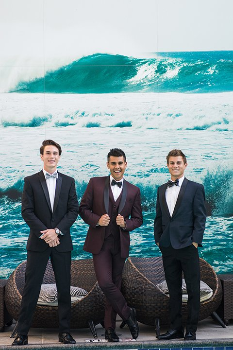 Downtown los angeles wedding shoot at the renaissance hotel groom black notch lapel tuxedo with white dress shirt and heather grey pipe edge bow tie and groomsmen navy blue shawl lapel tuxedo with blue striped bow tie with groomsmen burgundy shawl lapel tuxedo with matching vest and white dress shirt with black faux leather bow tie
