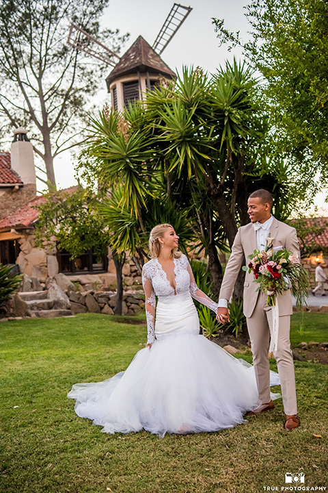 San diego outdoor wedding at mt woodson castle bride form fitting mermaid style gown with long lace sleeves and plunging neckline with groom tan notch lapel suit with a matchiing vest and white dress shirt with a white bow tie with white floral boutonniere holding hands and groom holding pink and burgundy floral bridal bouquet