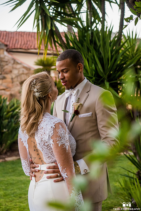 San diego outdoor wedding at mt woodson castle bride form fitting mermaid style gown with long lace sleeves and plunging neckline with groom tan notch lapel suit with a matchiing vest and white dress shirt with a white bow tie with white floral boutonniere hugging