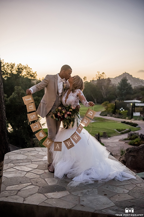 San diego outdoor wedding at mt woodson castle bride form fitting mermaid style gown with long lace sleeves and plunging neckline with groom tan notch lapel suit with a matchiing vest and white dress shirt with a white bow tie with white floral boutonniere kissing and holding just married sign
