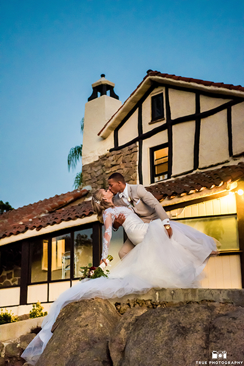 San diego outdoor wedding at mt woodson castle bride form fitting mermaid style gown with long lace sleeves and plunging neckline with groom tan notch lapel suit with a matchiing vest and white dress shirt with a white bow tie with white floral boutonniere hugging and bride holding pink and burgundy floral bridal bouquet
