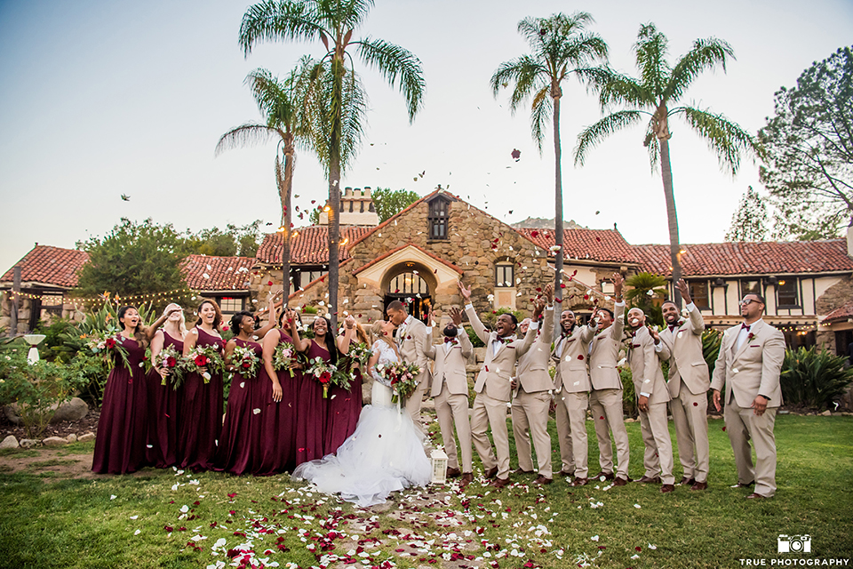 San diego outdoor wedding at mt woodson castle bride form fitting mermaid style gown with long lace sleeves and plunging neckline with groom tan notch lapel suit with a matchiing vest and white dress shirt with a white bow tie with white floral boutonniere kissing and bridal party throwing flower petals bridesmaids long burgundy dresses and groomsmen tan suits with burgundy bow ties