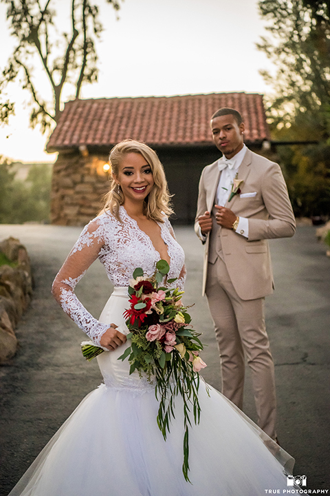 San diego outdoor wedding at mt woodson castle bride form fitting mermaid style gown with long lace sleeves and plunging neckline with groom tan notch lapel suit with a matchiing vest and white dress shirt with a white bow tie with white floral boutonniere standing and bride holding pink and burgundy floral bridal bouquet