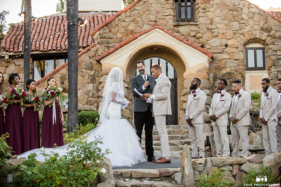 San diego outdoor wedding at mt woodson castle bride form fitting mermaid style gown with long lace sleeves and plunging neckline with groom tan notch lapel suit with a matchiing vest and white dress shirt with a white bow tie with white floral boutonniere holding hands and exchanging vows during ceremony