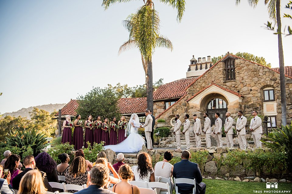 San diego outdoor wedding at mt woodson castle bride form fitting mermaid style gown with long lace sleeves and plunging neckline with groom tan notch lapel suit with a matchiing vest and white dress shirt with a white bow tie with white floral boutonniere holding hands during ceremony