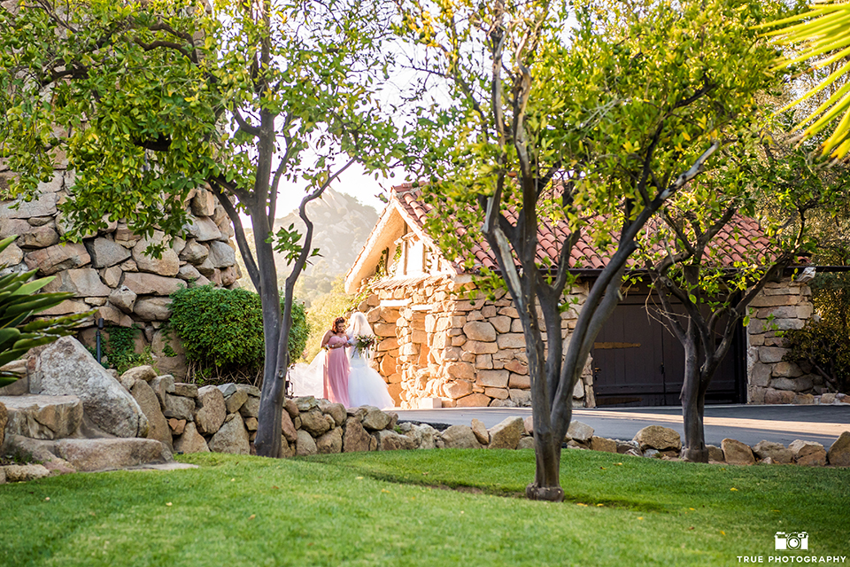 San diego outdoor wedding at mt woodson castle bride form fitting mermaid style gown with long lace sleeves and plunging neckline walking down the aisle
