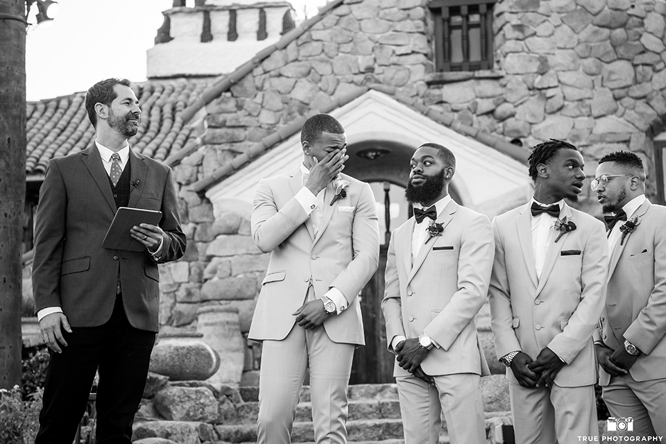 San diego outdoor wedding at mt woodson castle groom tan notch lapel suit with a matching vest and white dress shirt with a white bow tie and white floral boutonniere watching bride walk down the aisle crying black and white photo