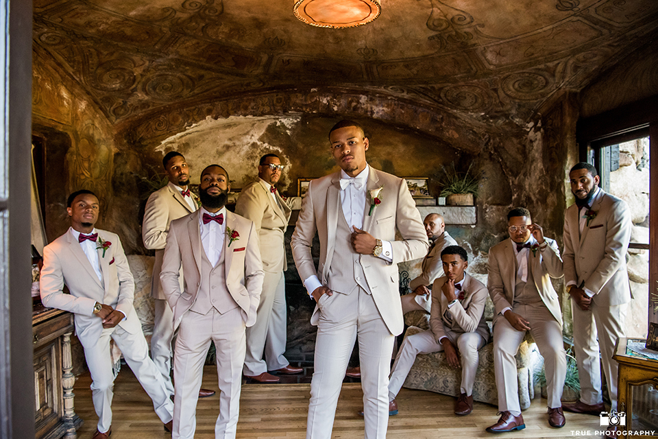 San diego outdoor wedding at mt woodson castle groom tan notch lapel suit with a matching vest and white dress shirt with a white bow tie and white floral boutonniere standing with groomsmen tan suits with burgundy bow ties
