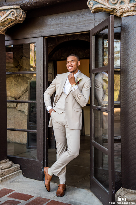 San diego outdoor wedding at mt woodson castle groom tan notch lapel suit with a matching vest and white dress shirt with a white bow tie and white floral boutonniere standing against wall
