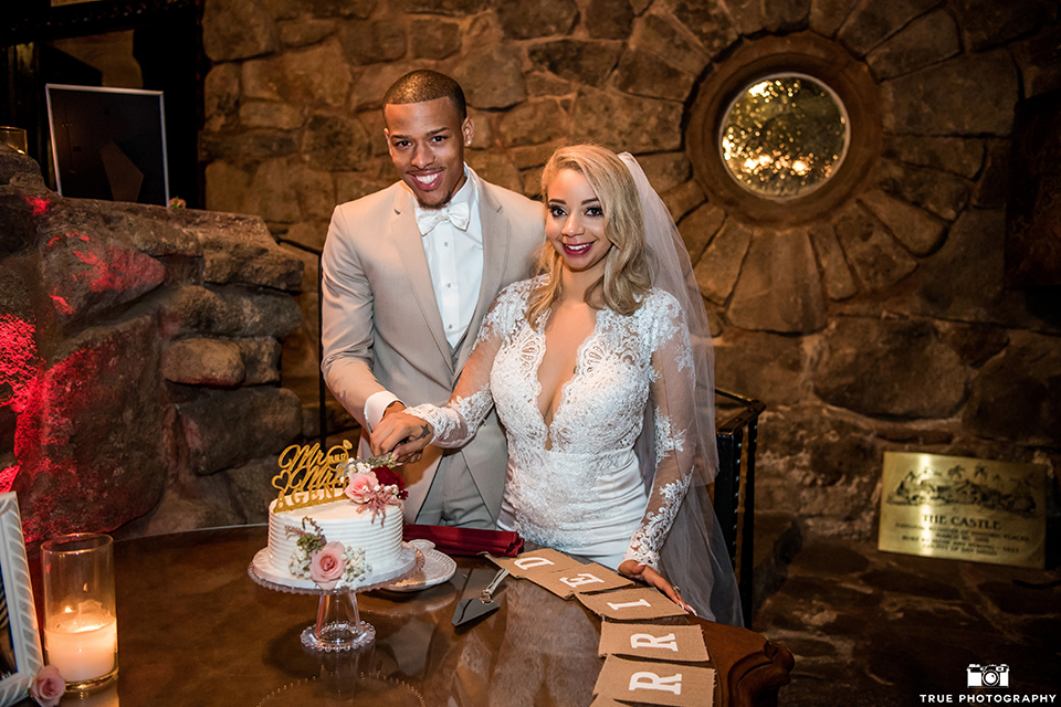 San diego outdoor wedding at mt woodson castle bride form fitting mermaid style gown with long lace sleeves and plunging neckline with groom tan notch lapel suit with a matchiing vest and white dress shirt with a white bow tie with white floral boutonniere cutting the cake at reception