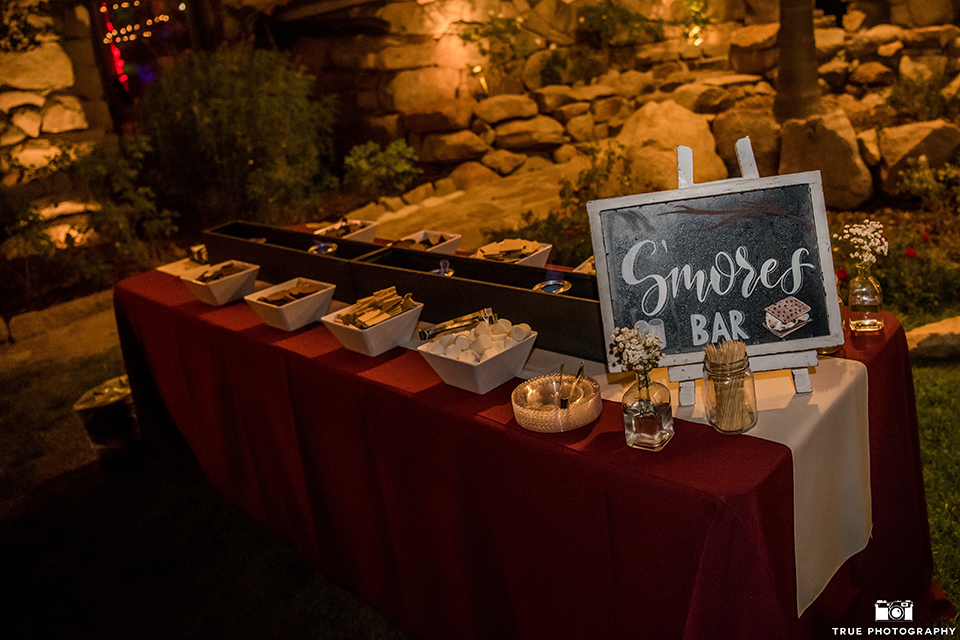 San diego outdoor wedding at mt woodson castle reception table set up with desserts smores bar with black and white sign with burgundy table linen wedding photo idea for desserts