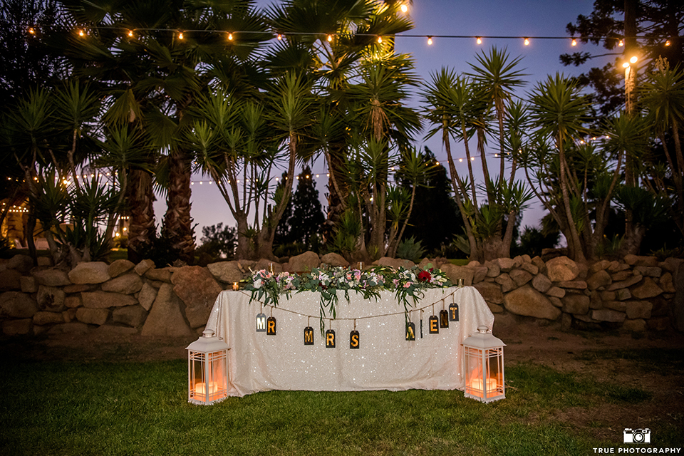 San diego outdoor wedding at mt woodson castle reception table set up sweetheart table with white table linen and hanging sign with candle lanterns on the ground with green and pink flower garland decor with burgundy linen napkins wedding photo idea