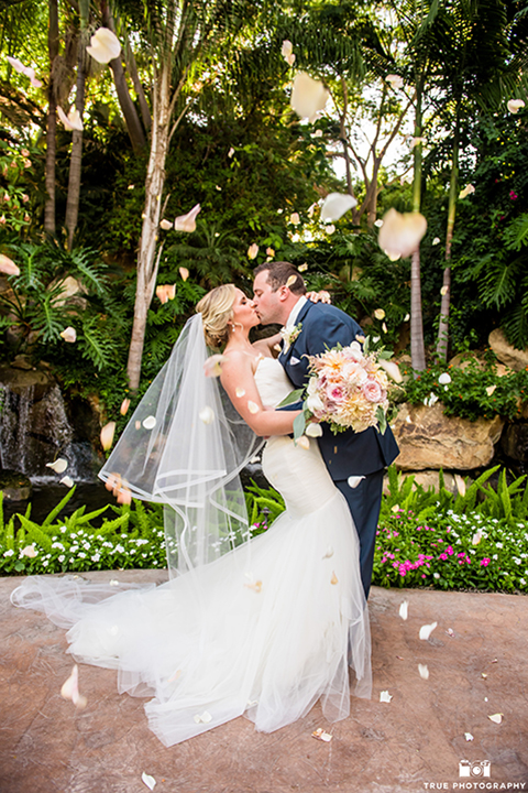 San diego outdoor wedding at the grand tradition estate bride form fitting mermaid style strapless gown with a crystal belt and groom navy blue notch lapel suit with a matching vest and white dress shirt with a long white tie and white floral boutonniere kissing and bride holding white and green floral bridal bouquet